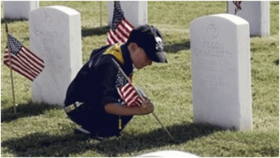 boy scout placing America flag at tombstones