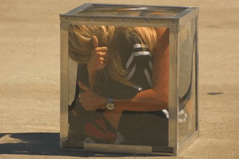 Human contortionist in a glass box