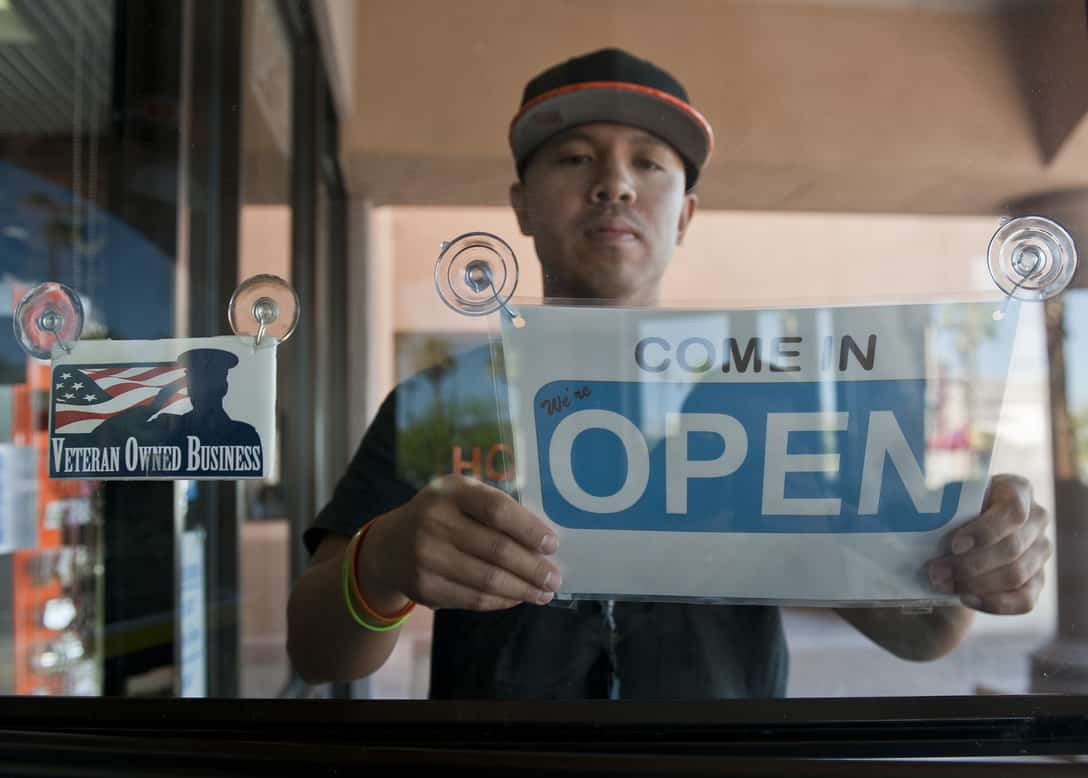 Man turning closed sign to open with a veteran owned business sticker in window