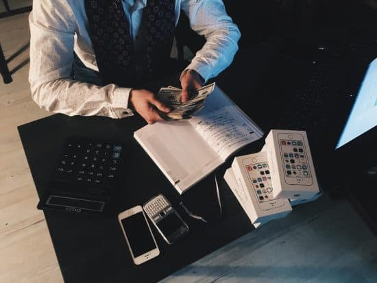 Man counting money with iPhones on desk