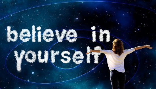 Woman standing with her arms spread wide in front of text saying Believe In Yourself