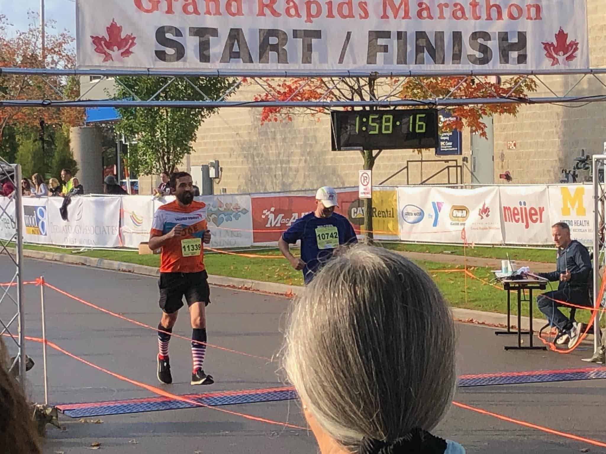 Joseph Lalonde in a Team World Vision jersey crossing the finish line of the Grand Rapids half marathon