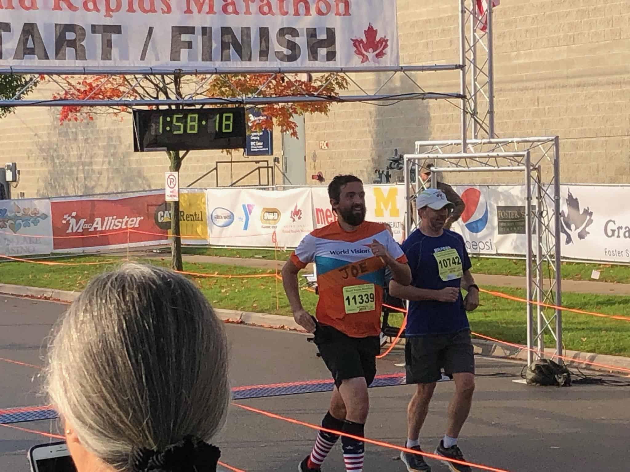 Runner in a Team World Vision jersey crossing the finish line of the Metro Health Grand Rapids half marathon