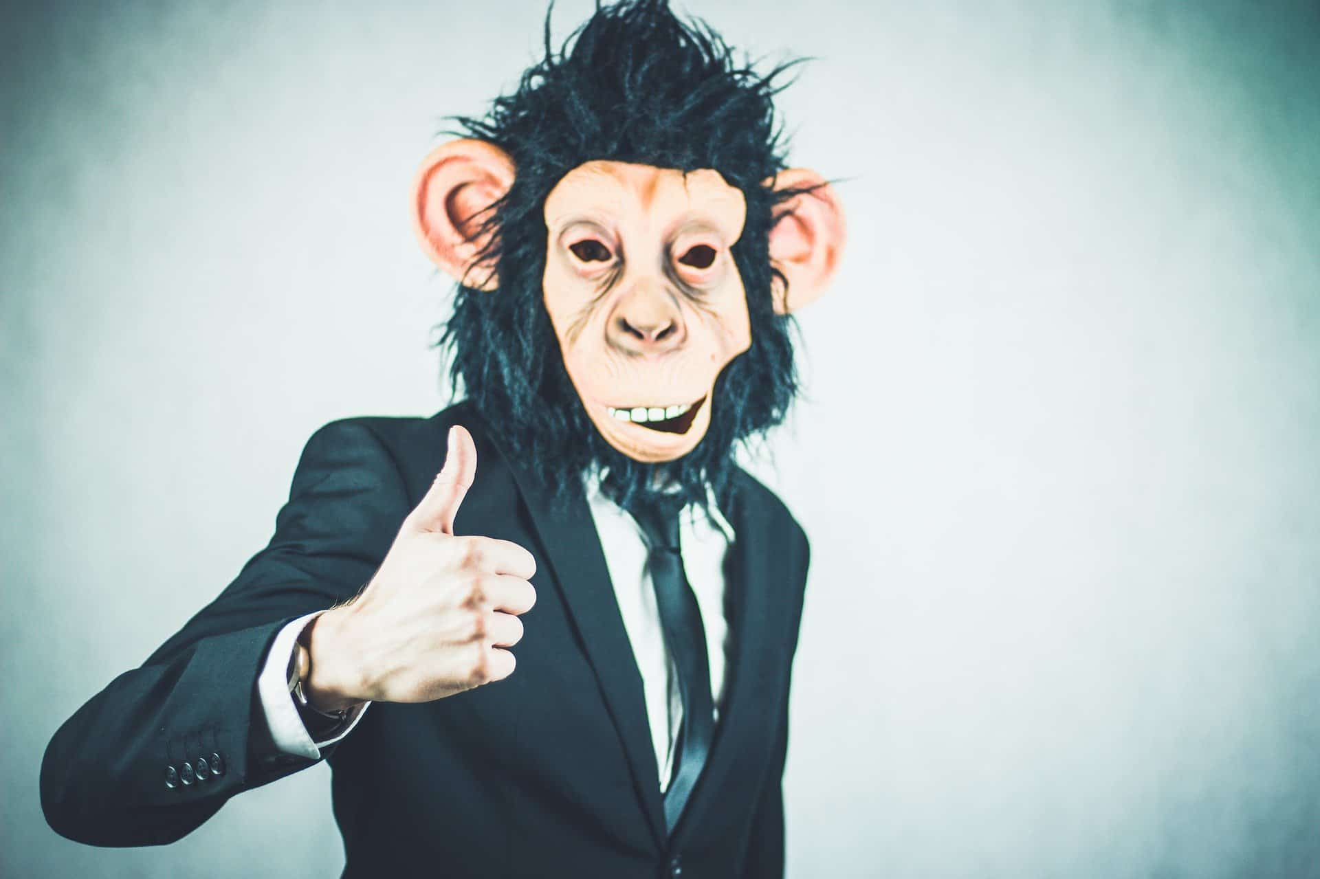 Man in a suit wearing a monkey head