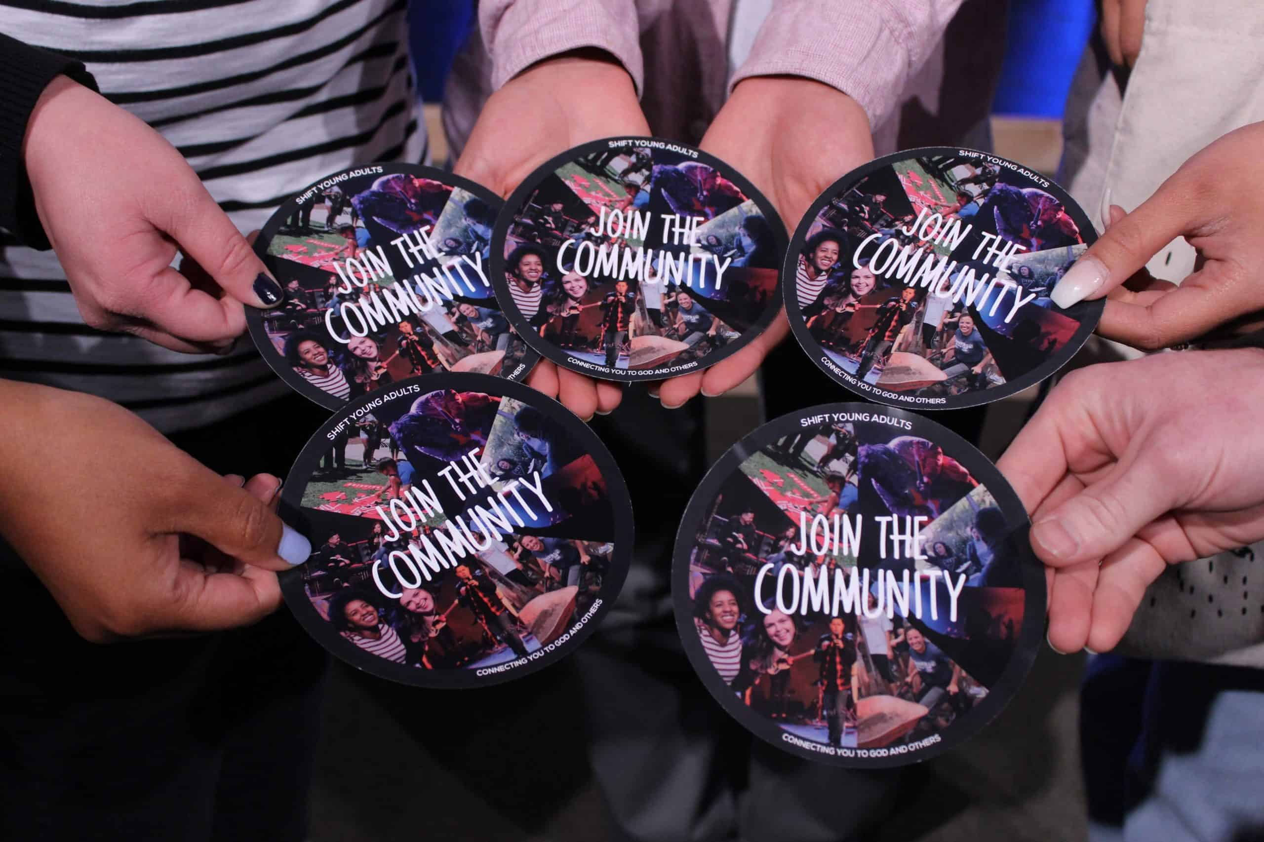 "Hands holding ""Join The Community"" buttons"