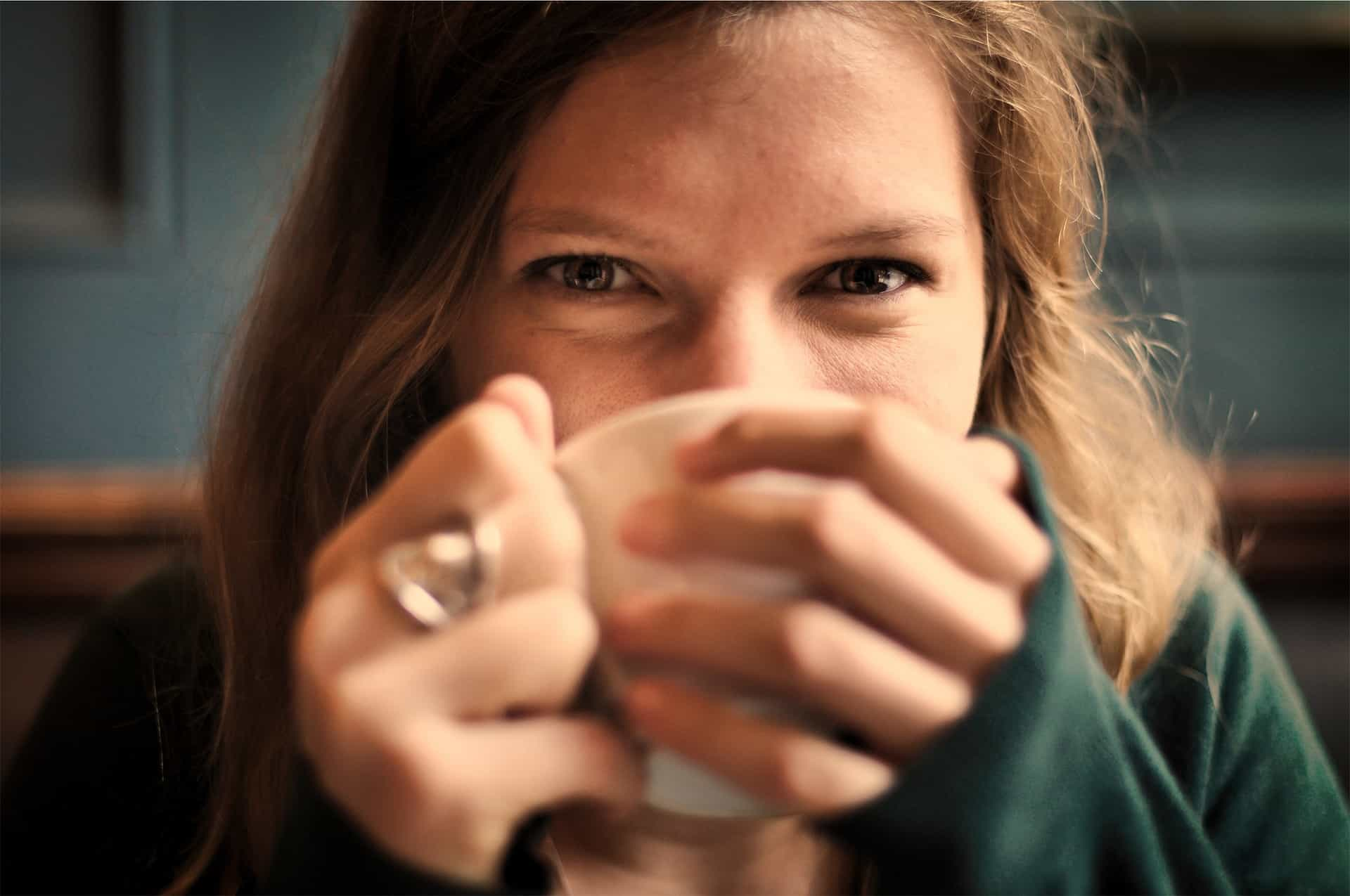 Woman smiling behind a cup of coffee