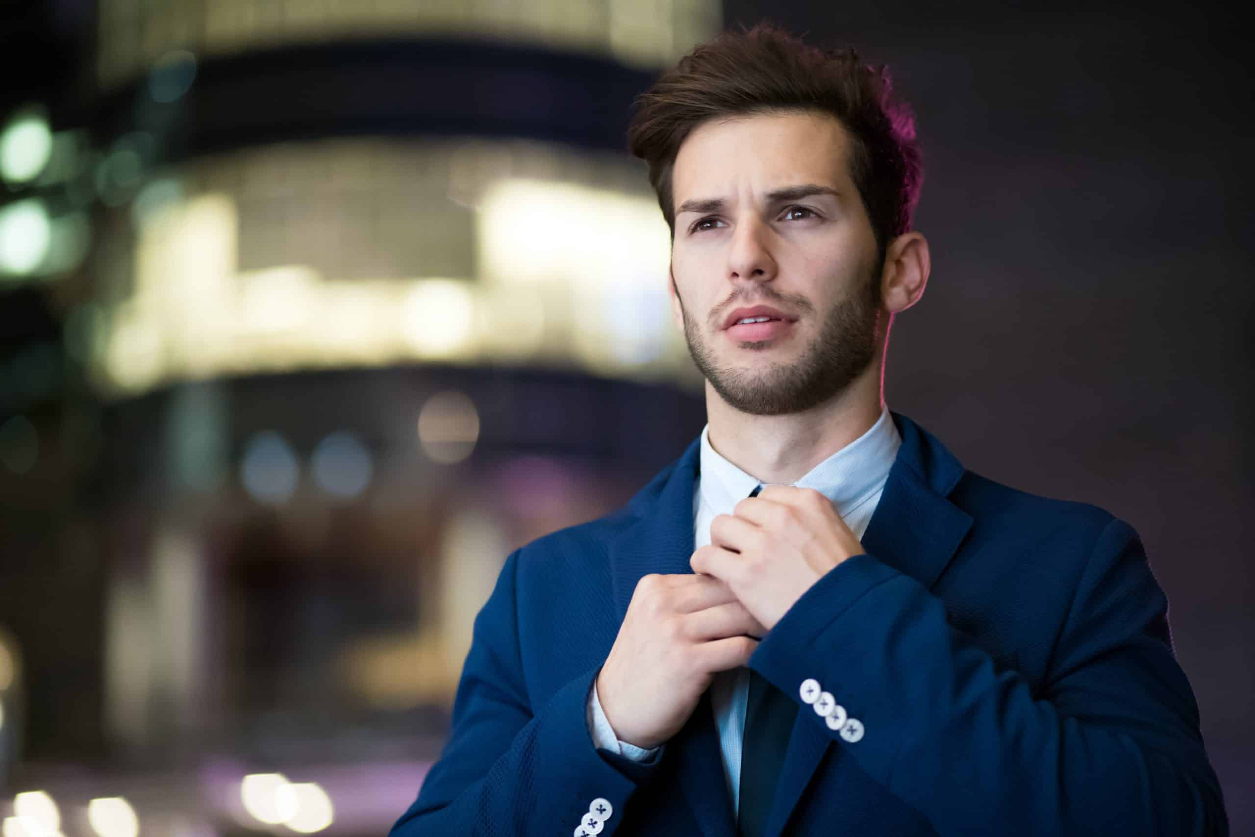 Man wearing a blue suit fixing tie