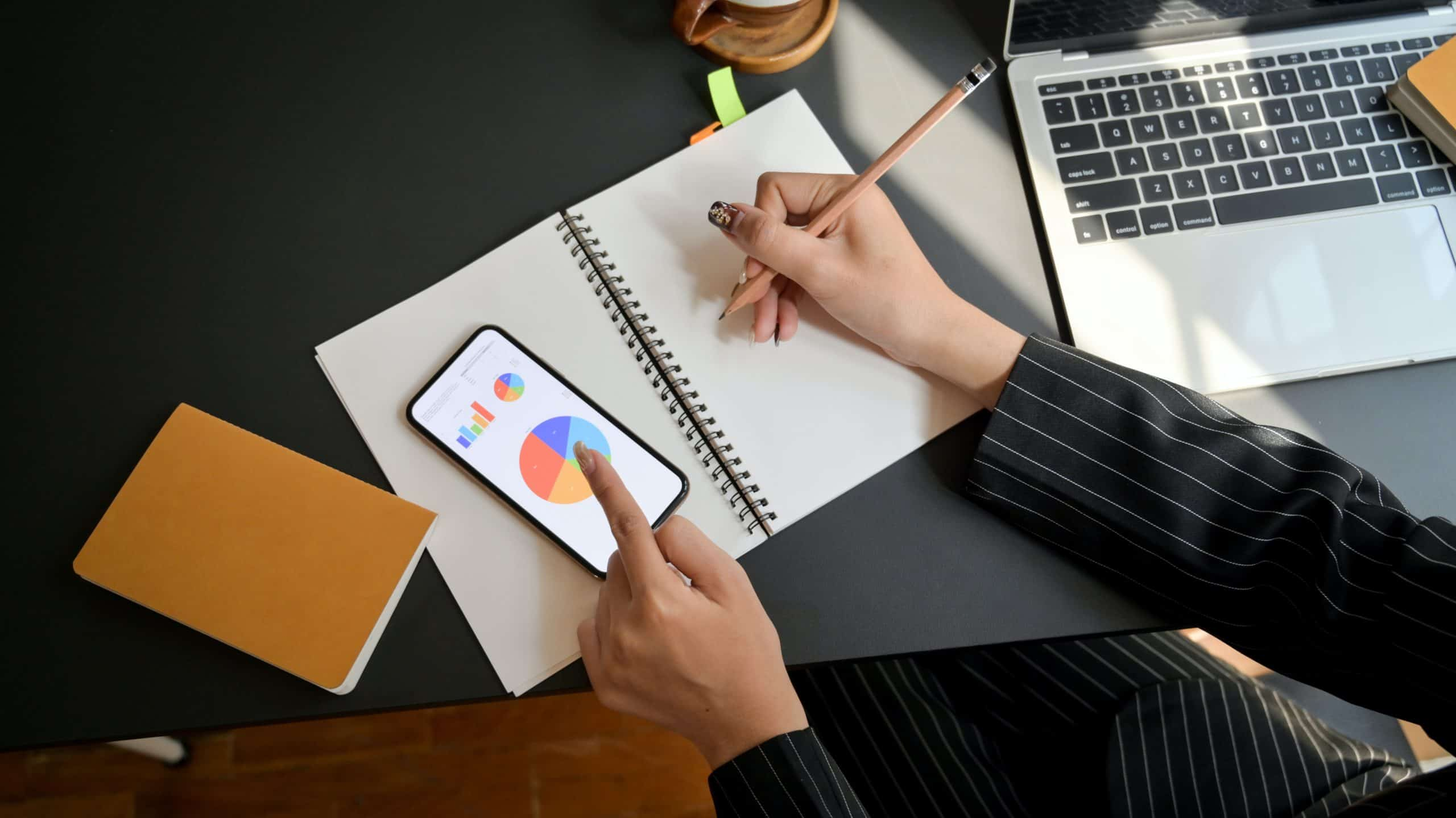 Man writing in a notebook with his iPhone next to him