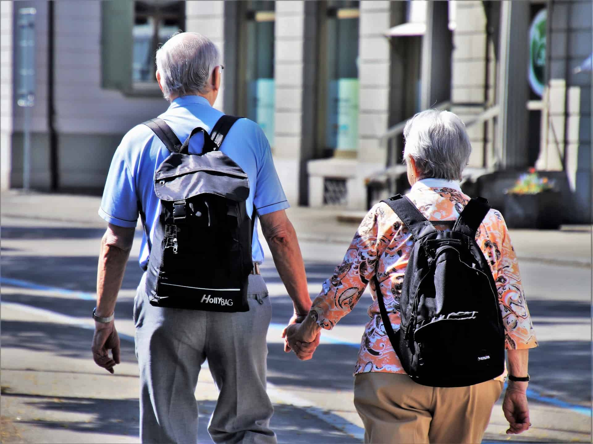 Two senior citizens holding hands while crossing the street