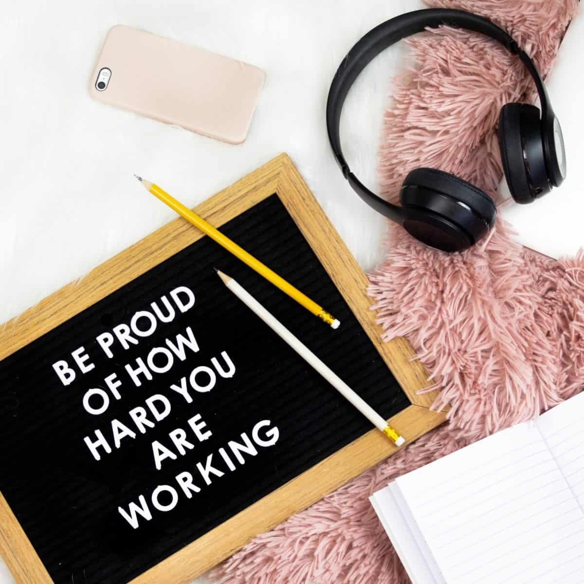 Black headphones with a sign saying Be Proud Of How Hard You Are Working