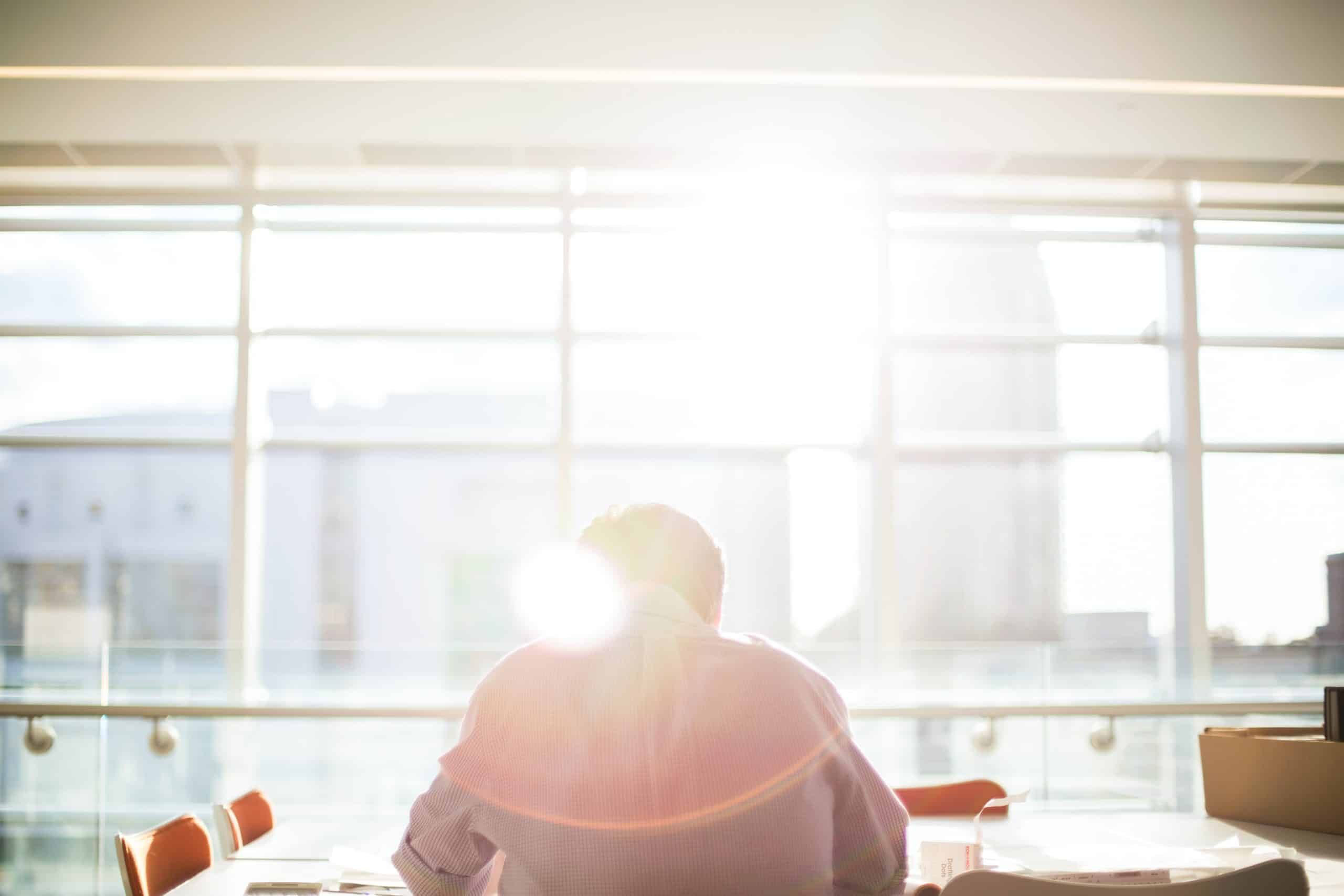 Man sitting at a window with the sun shining in