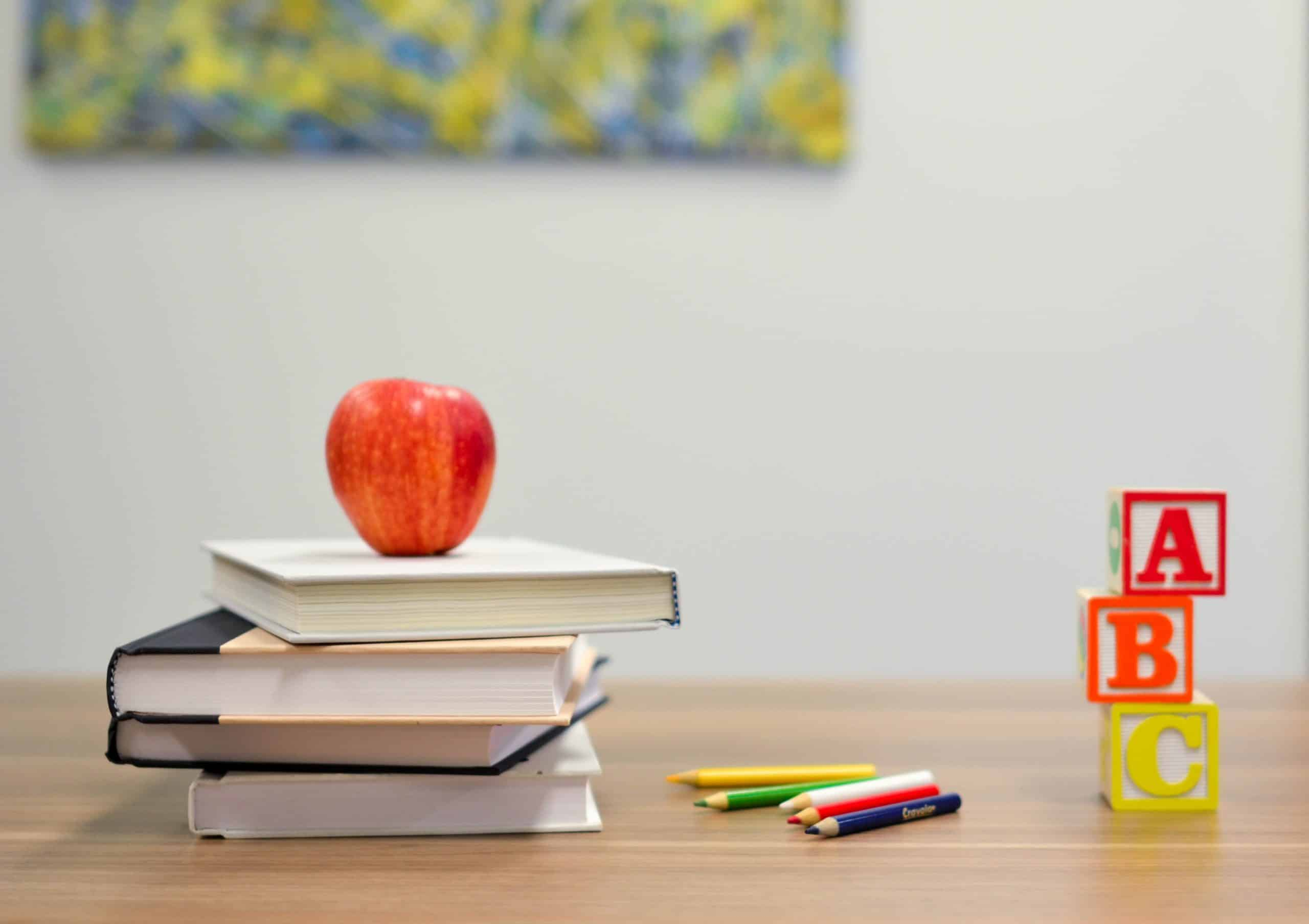 Books, apple, and pencils on a wooden desk